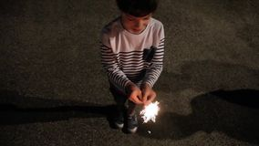 Happy kid holding sparkler outdoors in the night stock footage