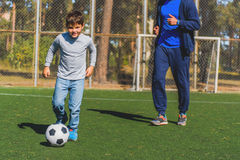 Happy kid kicking ball with joy. Carefree boy is playing football and smiling. His father is running to him on field Royalty Free Stock Photography