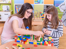Happy Kid and Kindergarten Teacher Playing with Toy Building Blocks Royalty Free Stock Images