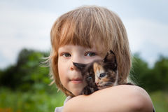 Happy kid with a kitten Stock Images