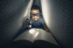 Happy kid laying on the bed under blanket holding flashlight and reading book late at night