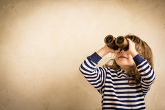Happy kid looking ahead. Smiling child with spyglass. Travel and adventure concept. Freedom, vacation Royalty Free Stock Photo