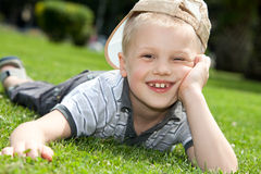 Happy kid lying on the grass stock photo