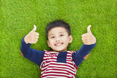 Happy kid lying and thumb up  on a meadow Royalty Free Stock Photos
