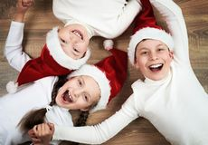 Happy kid lying together on wooden background, dressed in christmas Santa hat and having fun, happy new year and winter holiday co. Ncept stock images