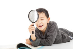 Happy kid with magnifying glass and book Royalty Free Stock Photo
