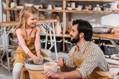 happy kid making ceramic pot on pottery wheel with teacher royalty free stock photo