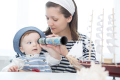 Happy kid and mom playing with toy sailing boat indoors. Stock Photography