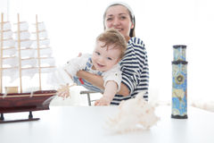 Happy kid and mom playing with toy sailing boat indoors. Royalty Free Stock Photo