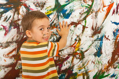 Happy kid painting with palms a wall Stock Photo