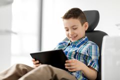 Happy kid patient with tablet pc at dental clinic. Medicine, dentistry and technology concept - happy kid patient with tablet pc computer at dental clinic Royalty Free Stock Photos