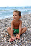 Happy kid on pebbly beach. Smiling boy in swimsuit with green/white floral pattern sitting on pebbly beach holding his feet with blue sea with waves and three Stock Photos