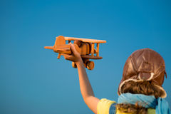 Happy kid playing with airplane outdoors Royalty Free Stock Image