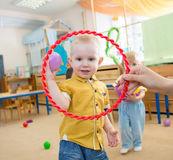 Happy kid playing with ball and ring in kindergarten Stock Images