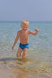 Happy kid playing on a beach Stock Photos