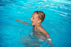 Happy kid playing in blue water of swimming pool. Royalty Free Stock Image