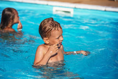 Happy kid playing in blue water of swimming pool. Royalty Free Stock Photos