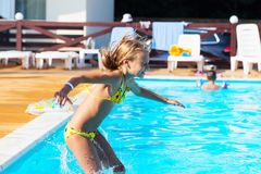 Happy kid playing in blue water of swimming pool. Little girl le Stock Images