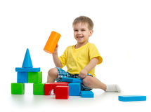 Happy kid playing with colorful building blocks on white. Background Royalty Free Stock Image