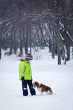 Happy kid playing with dog outdoors in winter day Royalty Free Stock Photos