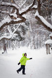 Happy kid playing with dog outdoors in winter day Royalty Free Stock Photo