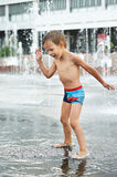 Happy kid playing in a fountain Royalty Free Stock Photos
