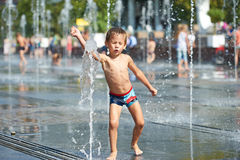 Happy kid playing in a fountain Stock Images
