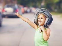 Happy kid playing in helmet outdoors Stock Photo