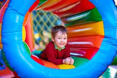 Happy kid playing on inflatable attraction playground Stock Photos