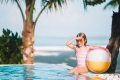 Smiling adorable girl playing with inflatable toy ball in outdoor swimming pool. Happy kid playing with inflatable toy ball in outdoor swimming pool on Maldives royalty free stock image