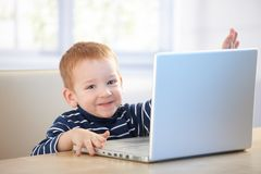 Happy kid playing with laptop at home Royalty Free Stock Photography