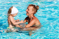 Happy kid playing with mother in swimming pool Royalty Free Stock Image