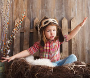 Happy kid playing in pilot helmet. Near the wooden background Royalty Free Stock Image