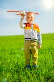 Happy boy playing with toy airplane against blue summer sky and green field background. Royalty Free Stock Photography