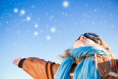 Happy kid playing with toy airplane. Against blue winter sky background stock photography