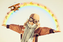 Happy kid playing with toy airplane. Against falling autumn maple leaves Stock Images