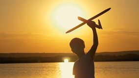 Happy child on a background of an orange sky and lake in summer at sunset, playing with a toy airplane. stock video