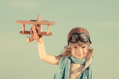 Happy kid playing with toy airplane. Against summer sky background. Travel and adventure concept Stock Photography
