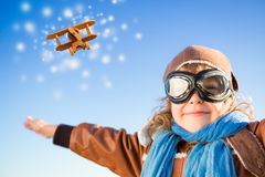 Happy kid playing with toy airplane in winter. Happy kid playing with toy airplane against blue winter sky background Stock Image