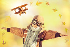 Happy kid playing with toy airplane. Happy kid playing with wooden toy airplane and falling maple leaves against autumn yellow blurred background Stock Images