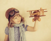 Happy kid playing with toy airplane. Happy kid playing with toy wooden airplane indoors Royalty Free Stock Images