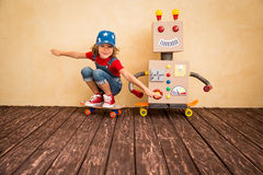 Happy kid playing with toy robot Stock Images
