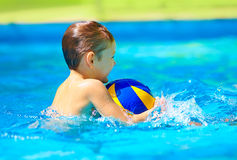 Happy kid playing water sport games in pool. Happy kid playing water sport games in the pool stock photo