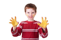 Happy Kid playing with yellow paint. Photo of an adorable child playing with yellow paint Royalty Free Stock Photo