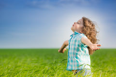 Happy kid with raised arms. In green spring field against blue sky. Freedom and happiness concept Stock Photos