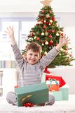 Happy kid raising arms at christmas. Happy kid sitting in pyjama on christmas morning, raising arms, getting christmas gift, laughing at camera Royalty Free Stock Photo