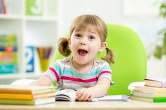 Happy kid reading book at table in nursery Stock Images