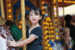 Happy kid riding a merry-go-round. Happy asian little kid riding a merry-go-round in the amusement park Stock Photography