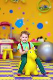 Happy kid riding a toy in kindergarten Royalty Free Stock Images