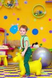 Happy kid riding a toy in kindergarten Stock Photo